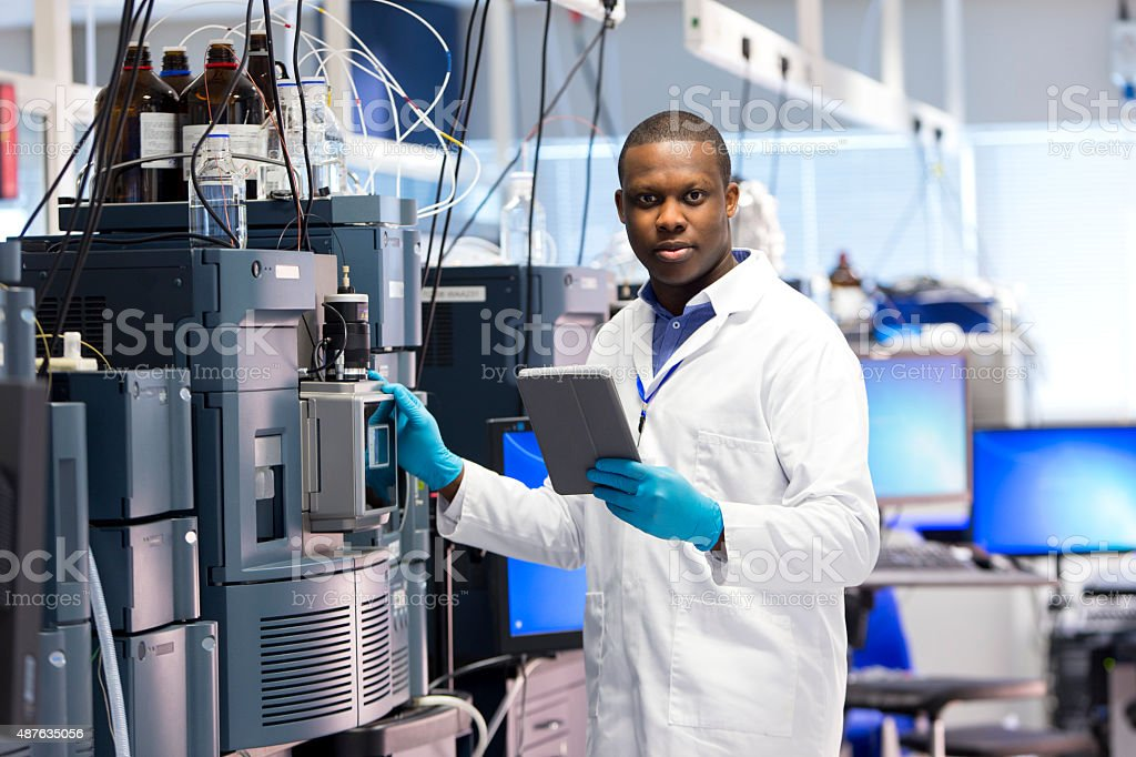 Male Working with Specialist Scientific Equipment for Measuring Chemicals. stock photo