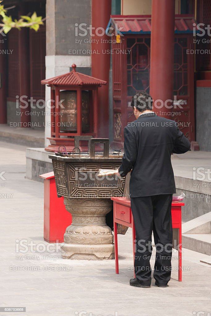 Male worshipper at large incense burner at Beijing Lama Temple stock photo