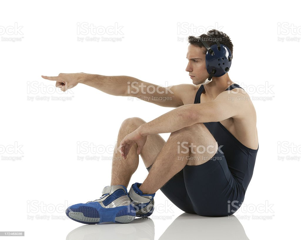 Male wrestler sitting on the floor and pointing royalty-free stock photo