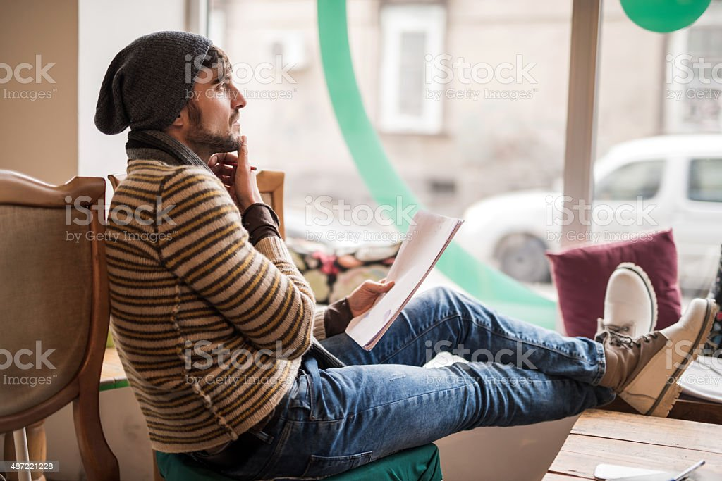 Male writer thinking of a headline for his new book. stock photo