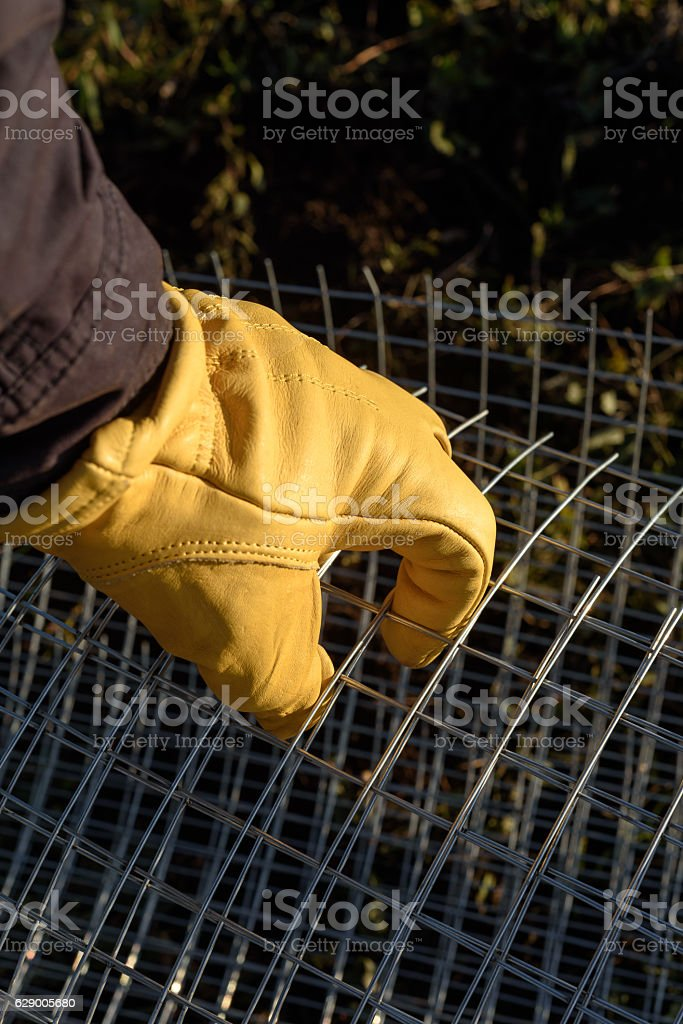 Male Yellow Gloved Hand Handling Chicken Wire stock photo