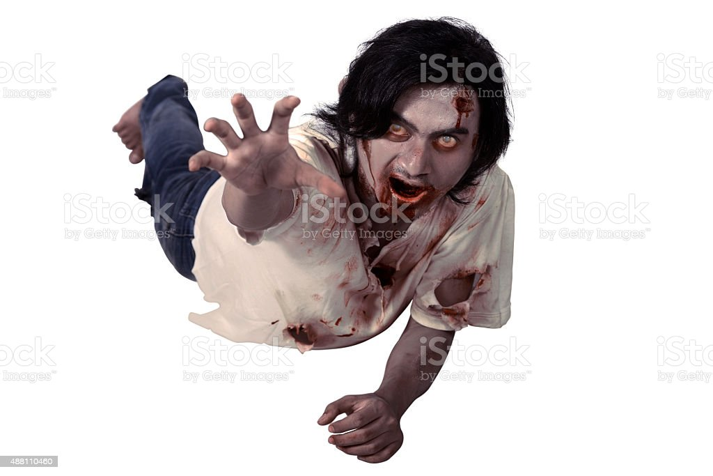 Male zombie crouching on the floor stock photo