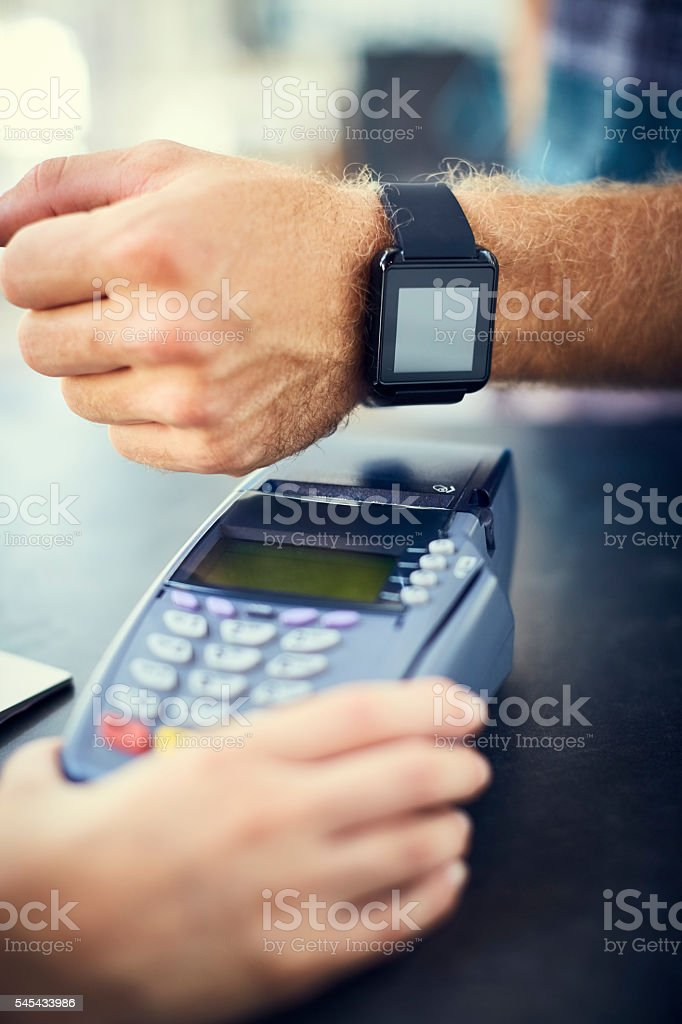 Male's hand paying through smart watch stock photo