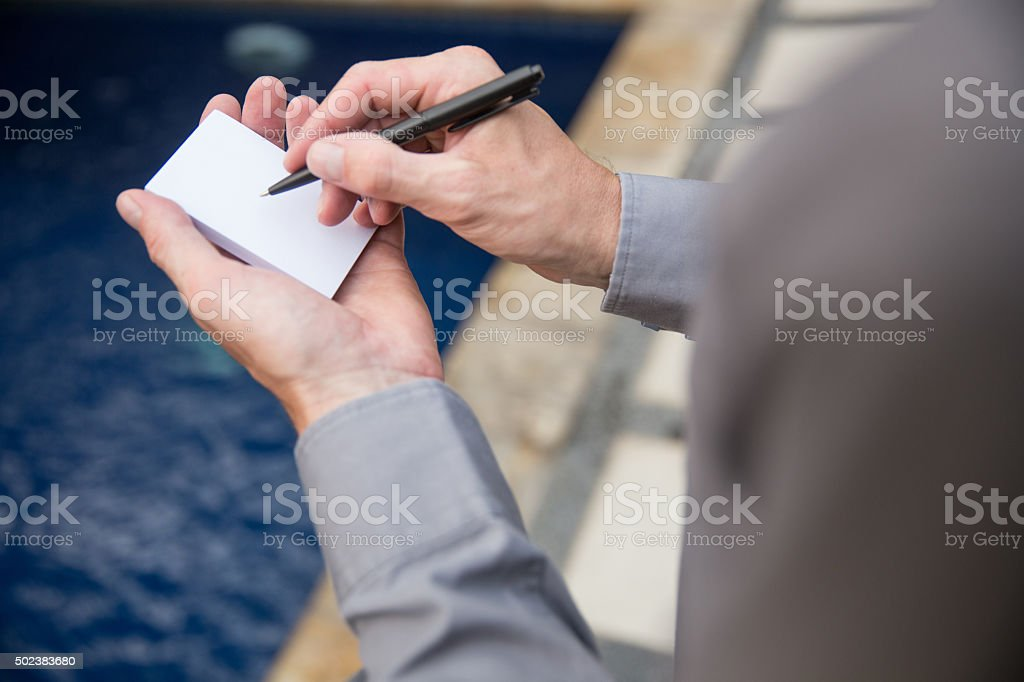 Males hands jotting on white paper stock photo