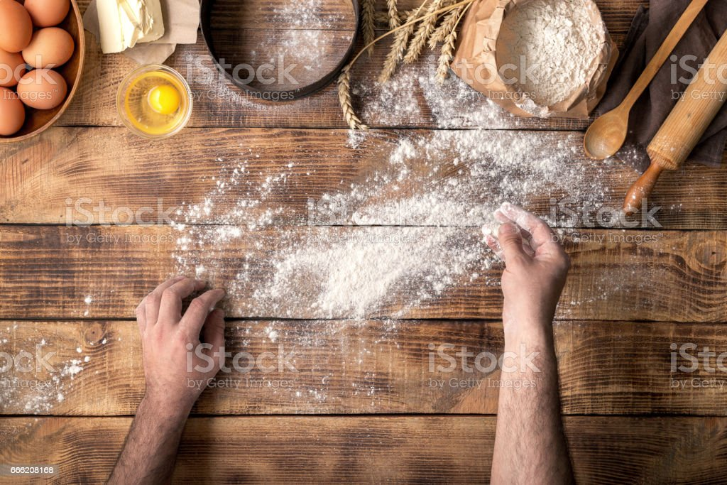 Males hands sprinkle with flour a wooden table for making dough stock photo