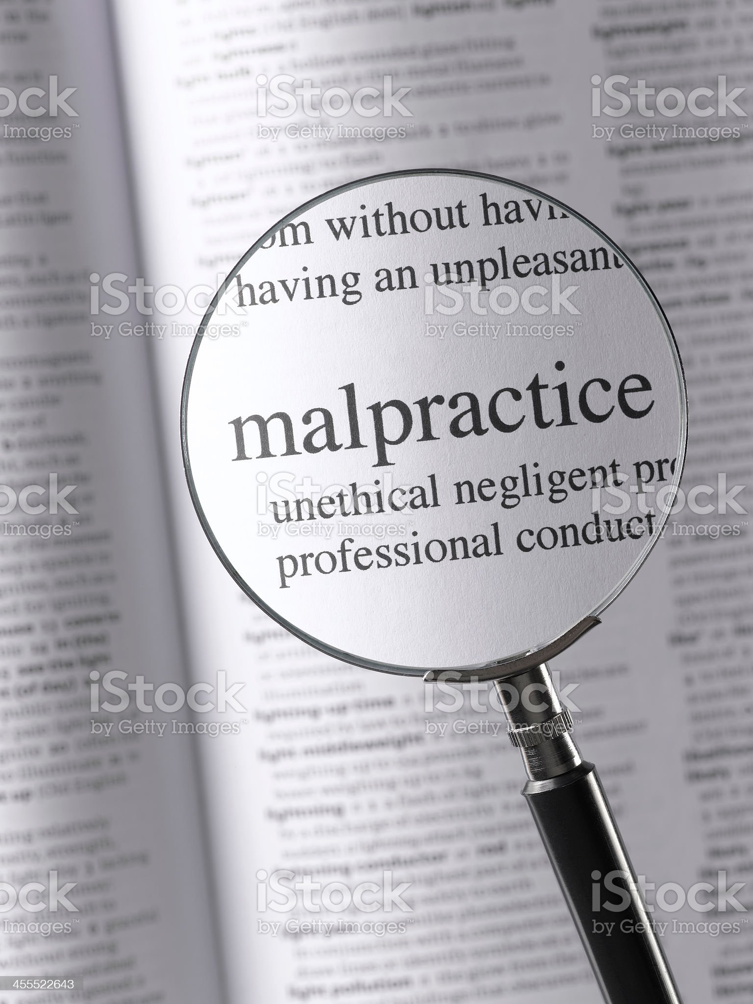 Malpractice printed on newspaper under a magnifying glass royalty-free stock photo