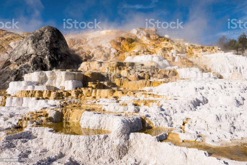 Mammoth hot springs travertine terraces in Yellowstone National Park with steam and step pools stock photo