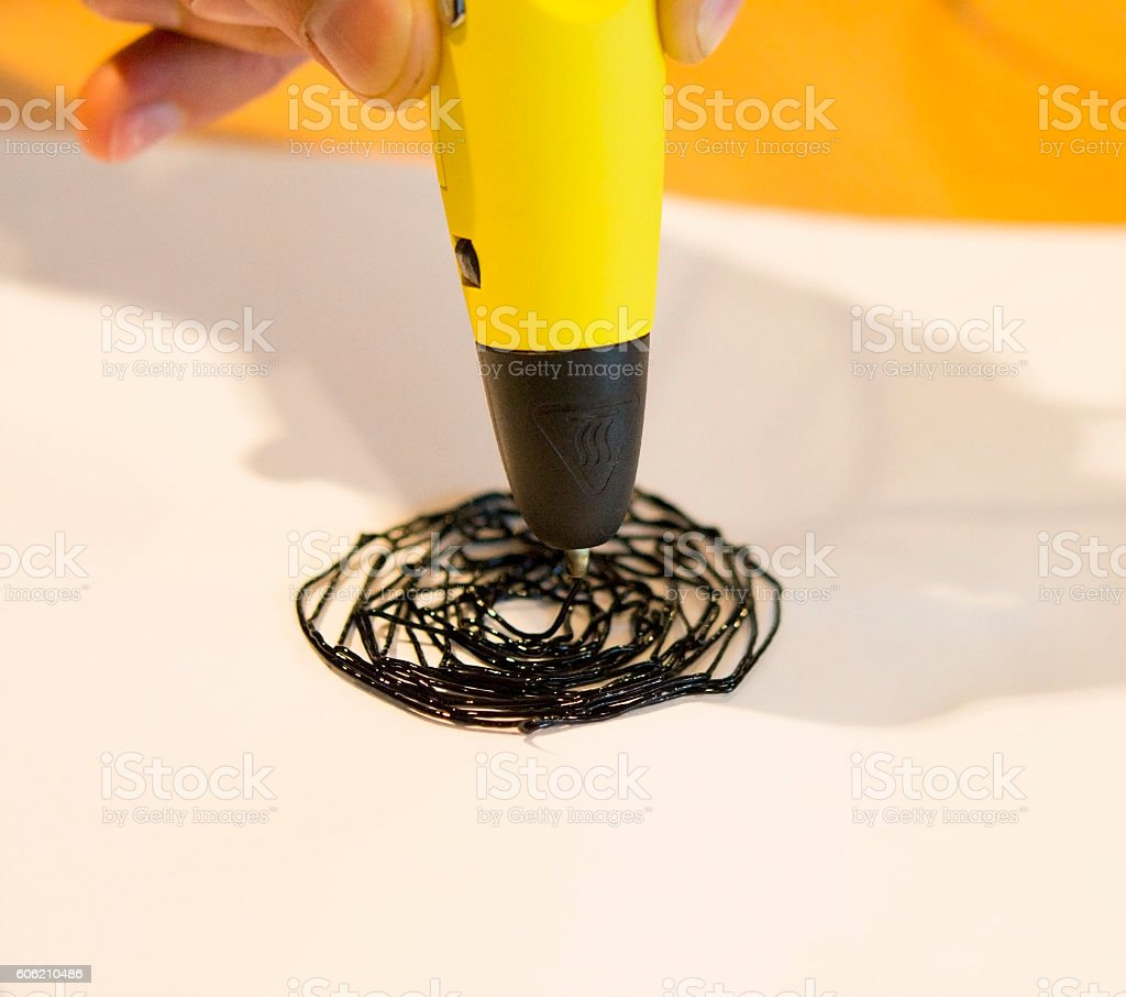 Man 3d pen draws a circle on white paper stock photo