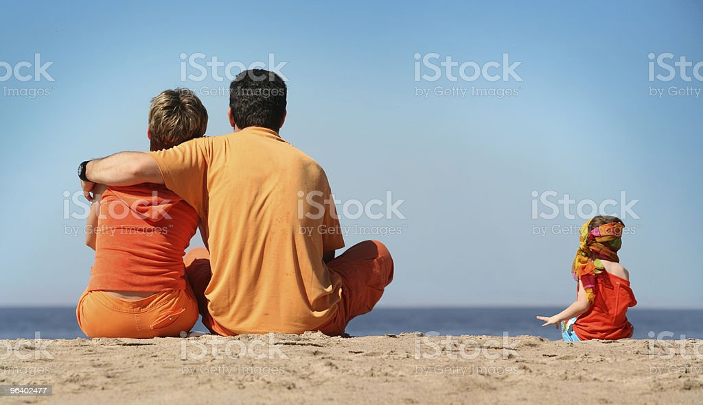 A man, a woman and a girl sitting on the sand at the beach stock photo