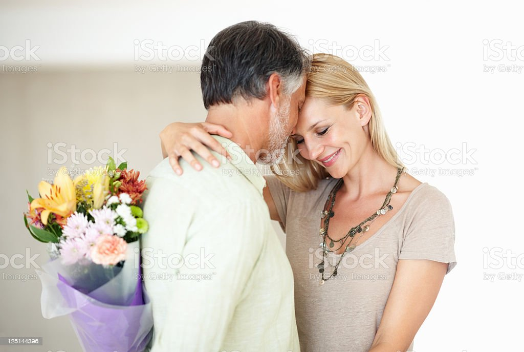 Man about to surprise lovely woman with flowers royalty-free stock photo