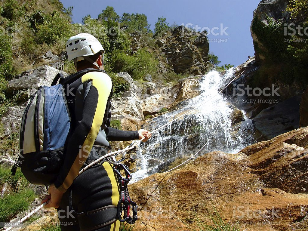 Man abseiling down a waterfall wearing protective gear stock photo