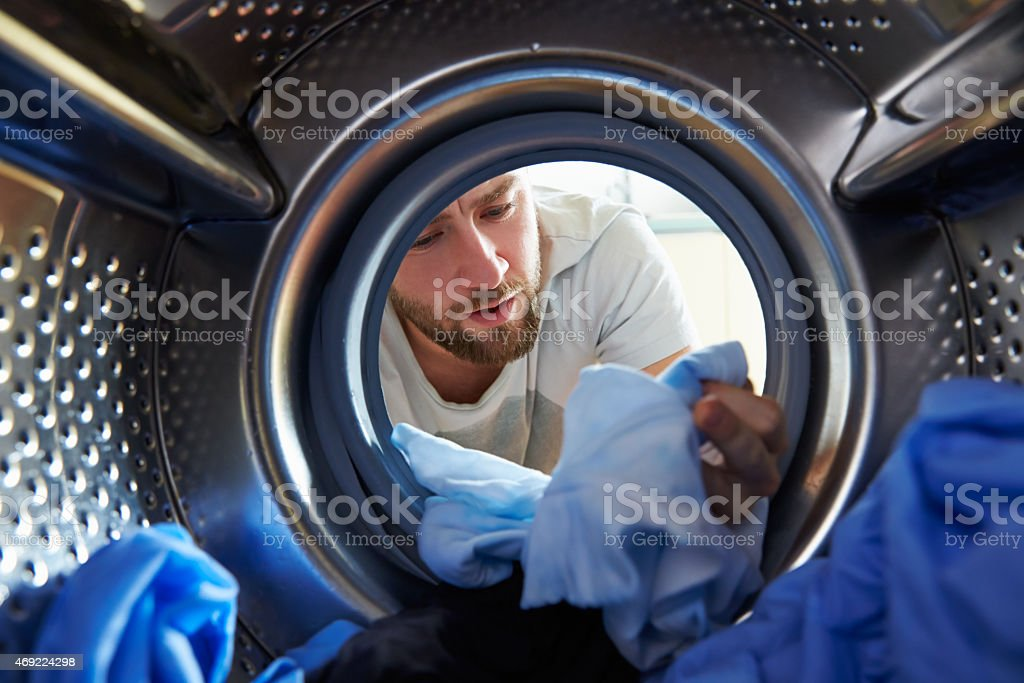 Man Accidentally Dyeing Laundry Inside Washing Machine stock photo