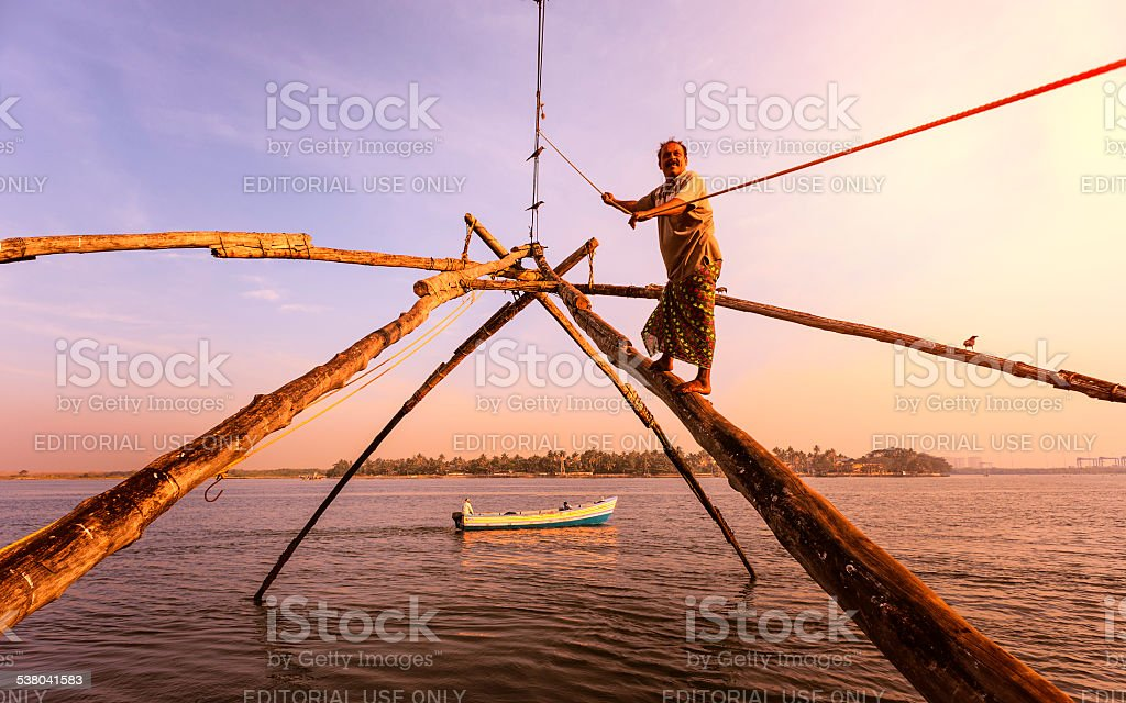 Man acts as cantilever weight for Chinese fishing net. stock photo