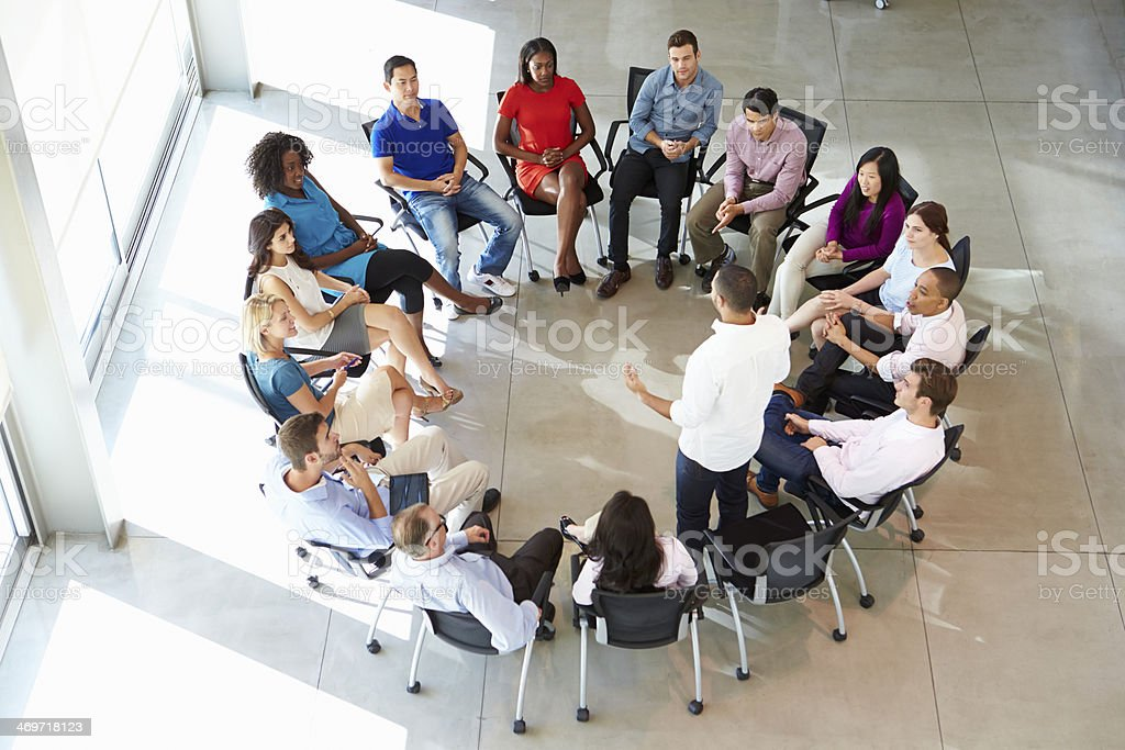 Man addressing muti-cultural office staff seated in circle stock photo
