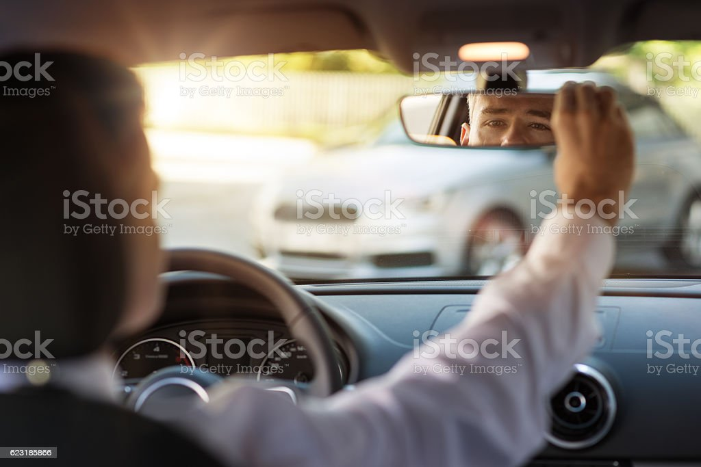 Man adjusting a rearview mirror stock photo