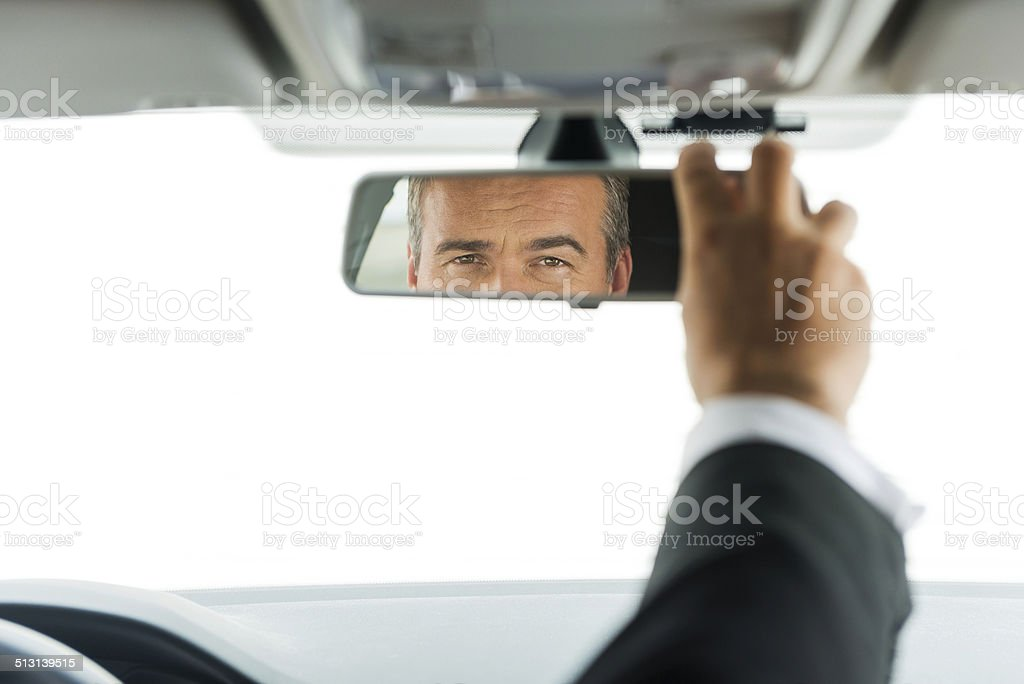 Man adjusting car mirror. stock photo