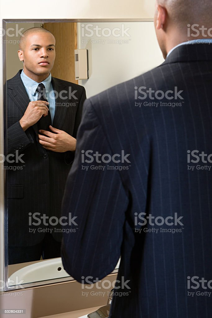 Man adjusting his tie in mirror stock photo