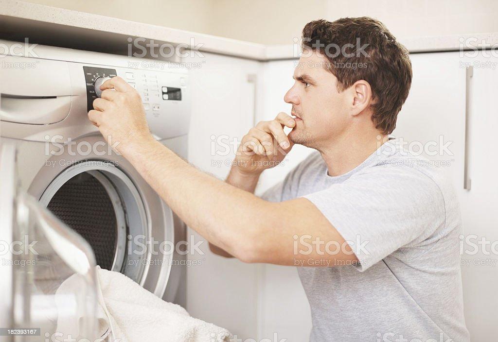 Man adjusting the controls of washing machine royalty-free stock photo