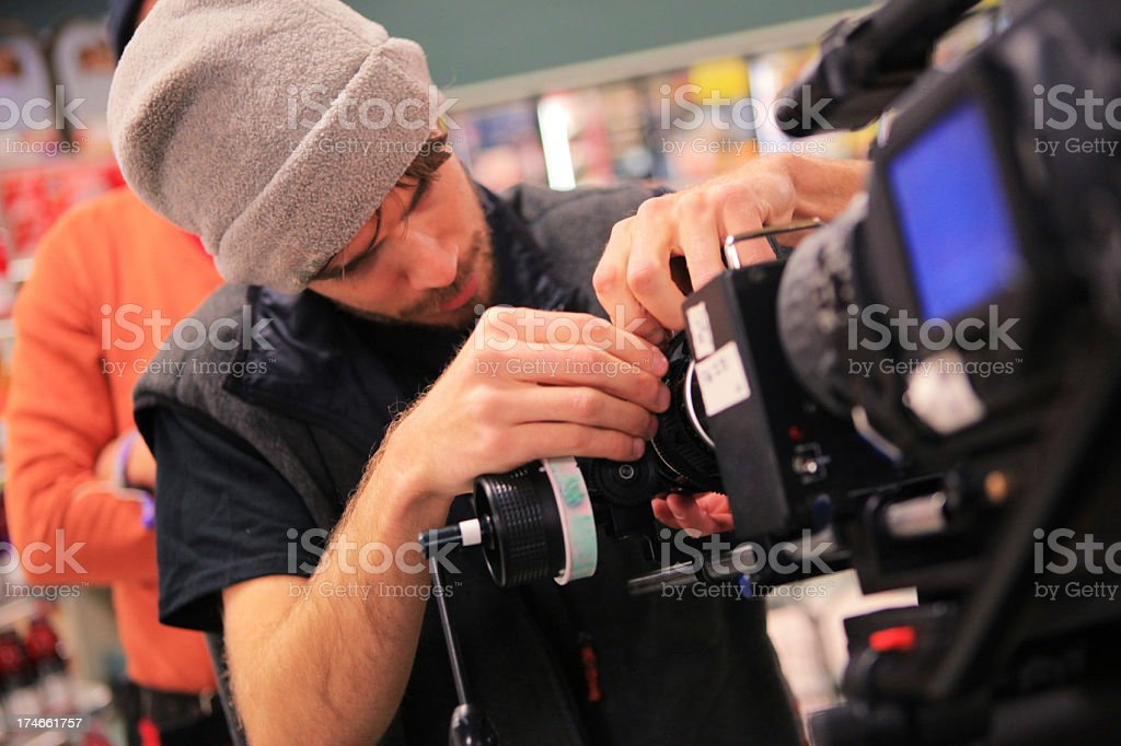 A man adjusting the settings on a camera stock photo