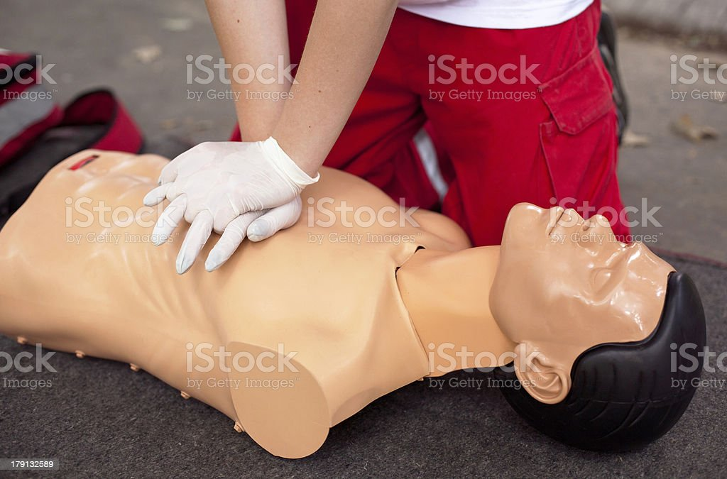 Man administrating CPR on a mannequin stock photo