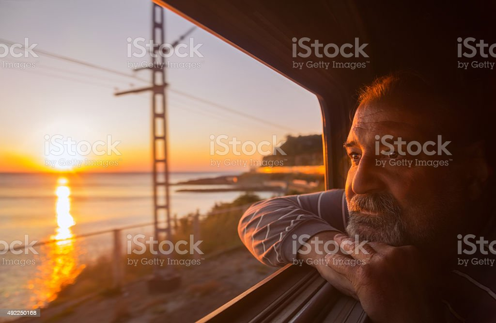 Man admires sea sunset from train stock photo