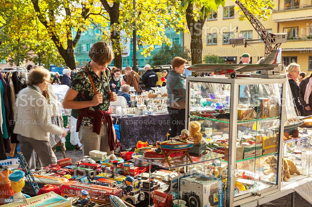 Man admiring stand with vintage tin toys on outdoor market. stock photo