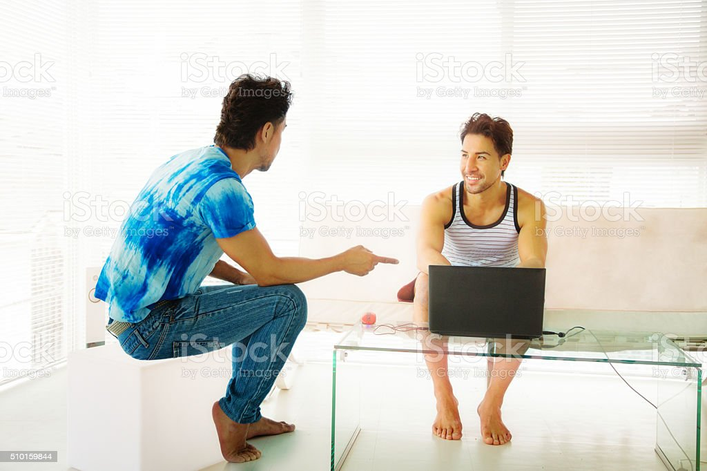 Man advising friend using laptop stock photo