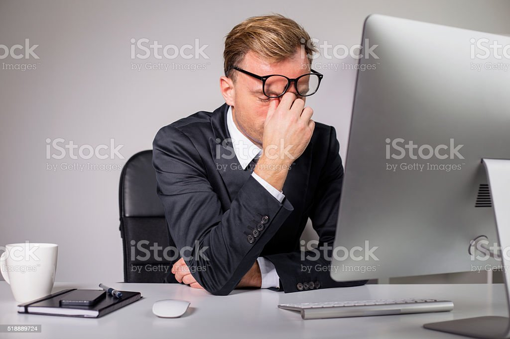 Man after long day holding his glasses stock photo