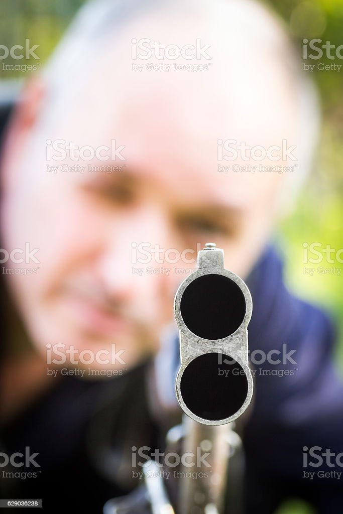 Man aiming a shotgun stock photo