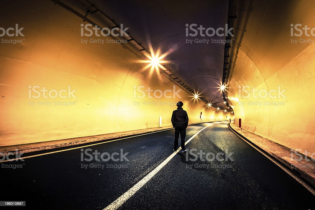 Man Alone in Middle of the Road at Night stock photo
