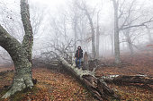 Man alone in mysterious and mystic forest in misty haze