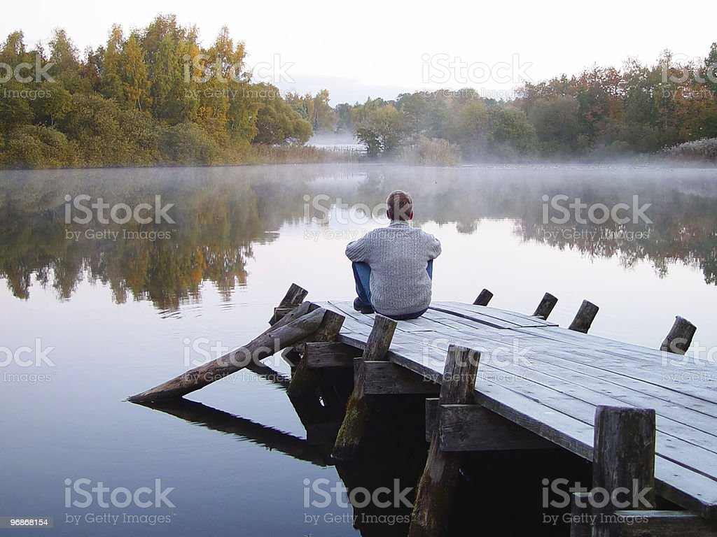 man alone on a pier with early morning mist stock photo