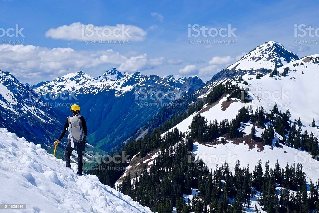 Man Alpinist Standing on Mountain Top. stock photo
