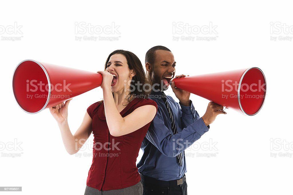 A man and a woman each shouting into a megaphone royalty-free stock photo