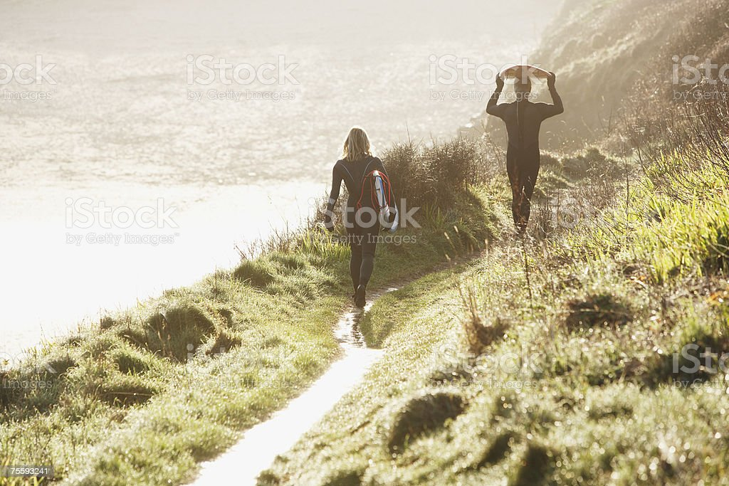 A man and a woman heading down to the surf royalty-free stock photo