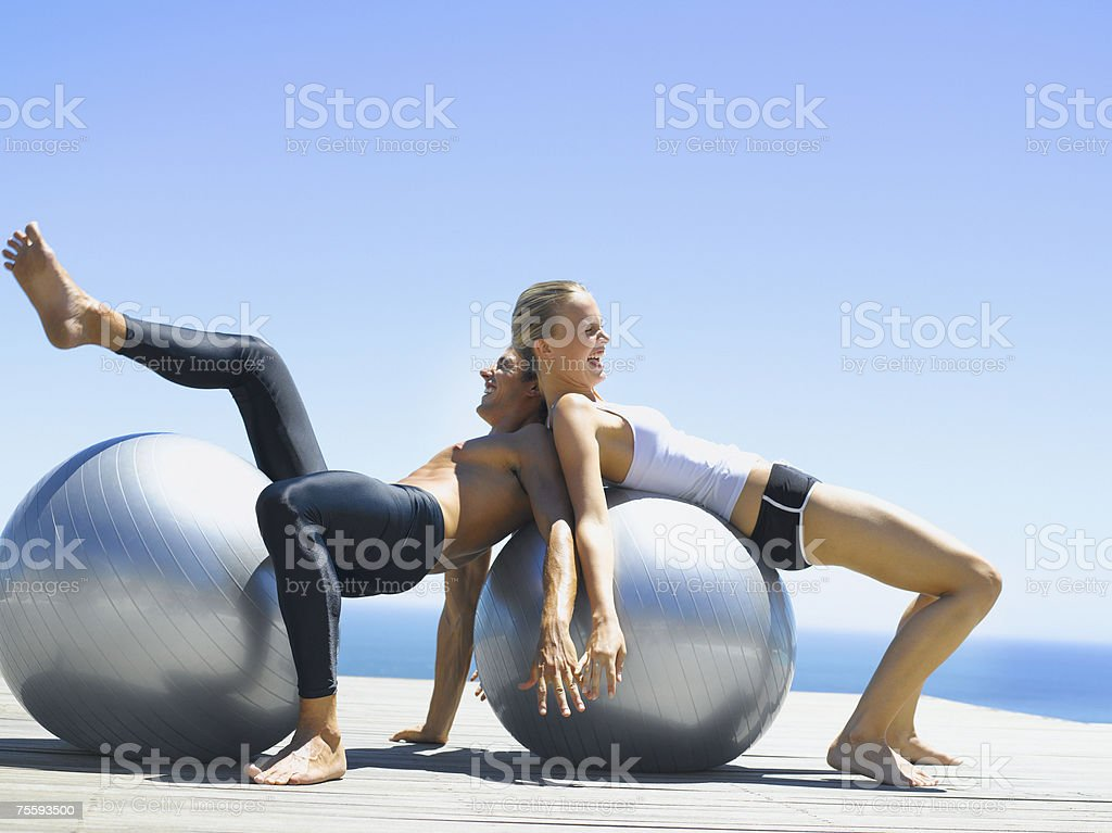 A man and a woman playfully working out with exercise balls royalty-free stock photo