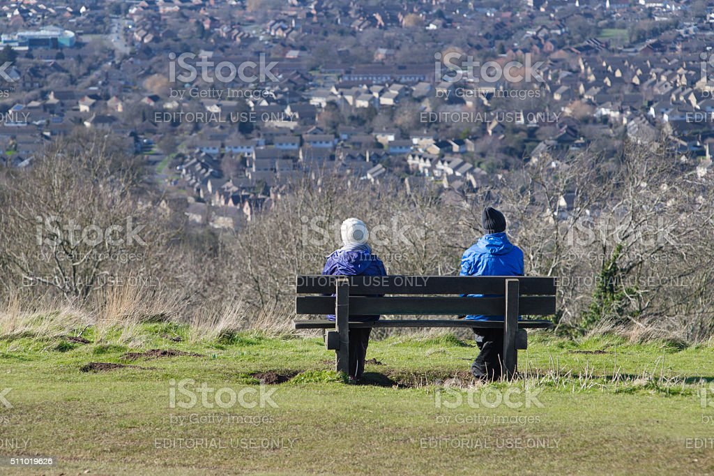Man and a woman sat on a bench stock photo
