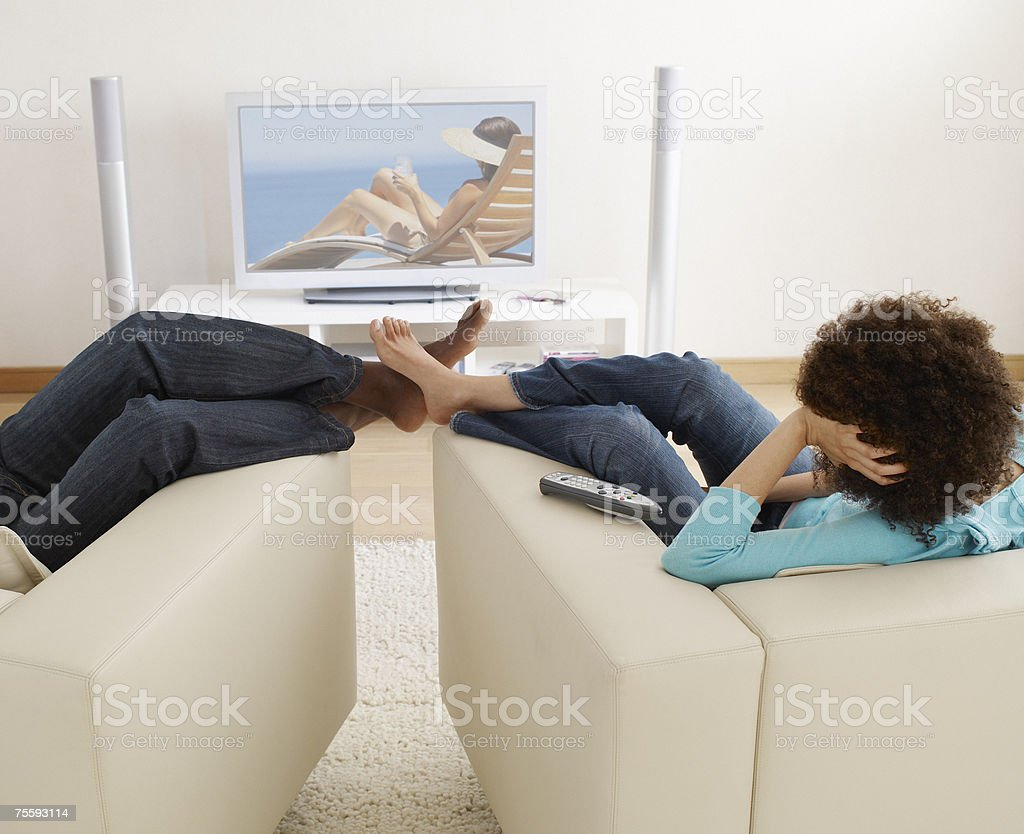 A man and a woman watching television royalty-free stock photo