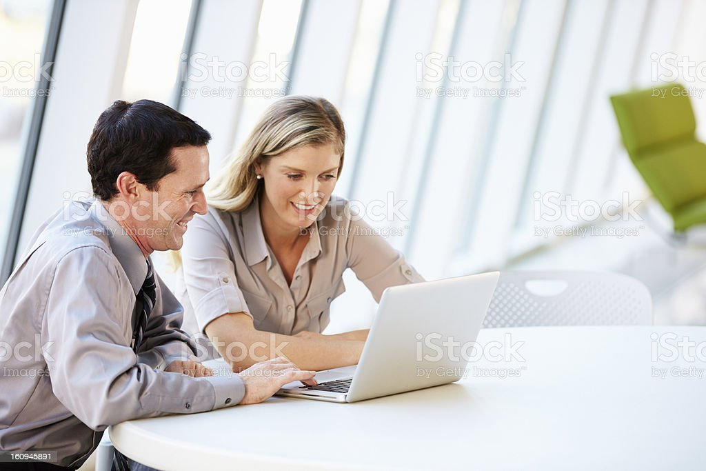 A man and a woman work in front of a laptop in an office stock photo