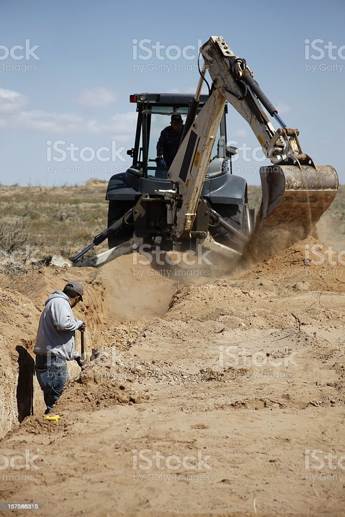 Man and Backhoe Working on Septic System Installation royalty-free stock photo