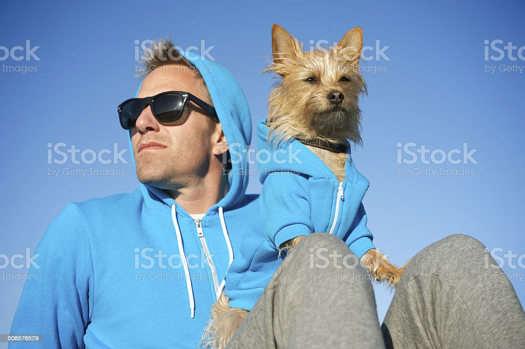 Man and Best Friend Dog in Matching Blue Hoodies stock photo