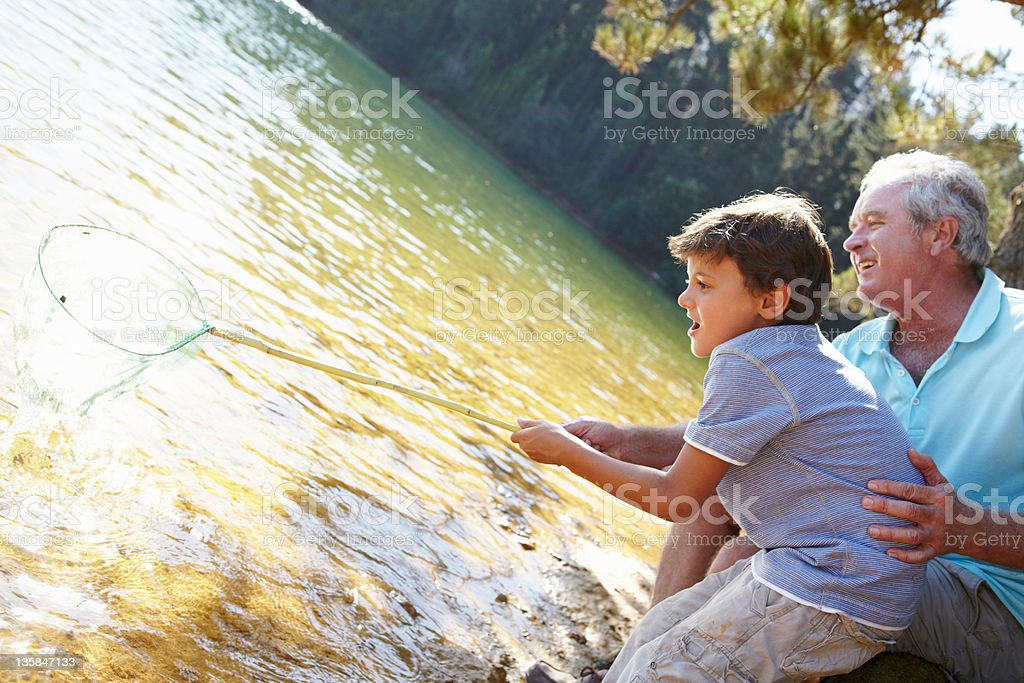 Man and boy fishing together stock photo
