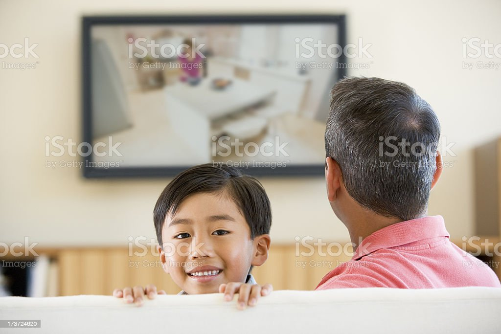 Man and boy in living room with flat screen television royalty-free stock photo