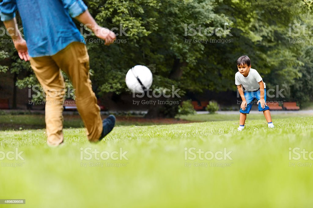 Man and boy playing football in the park stock photo