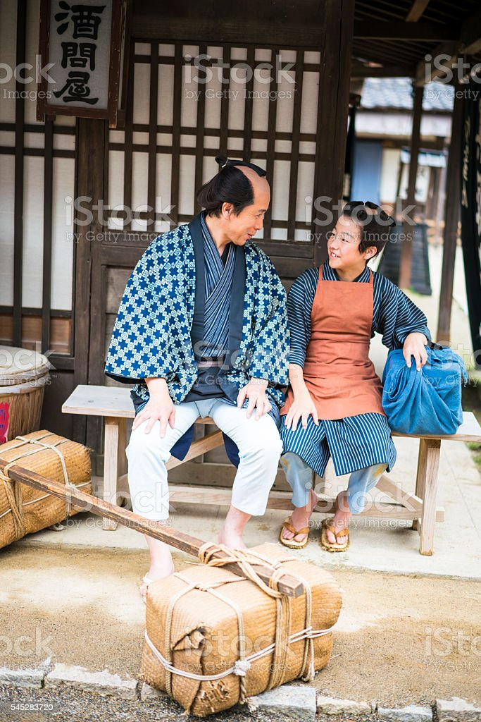 Man and boy talking while resting on old street, Japan stock photo