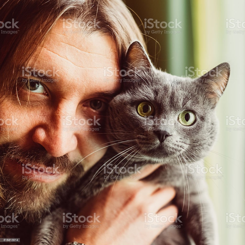 Man and cat looking at camera stock photo
