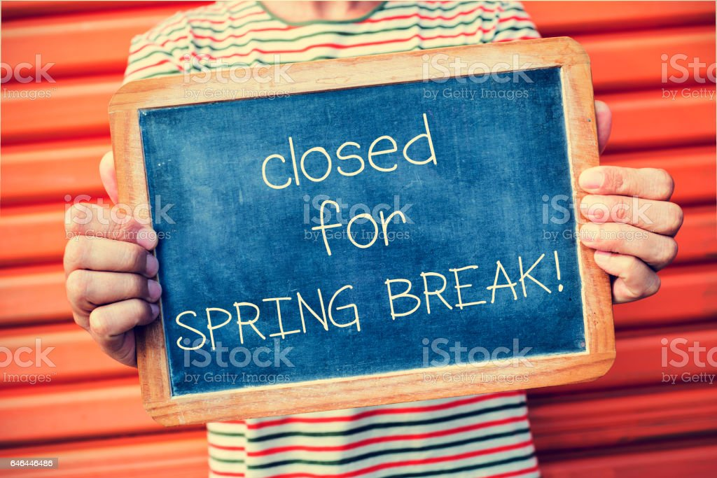 man and chalkboard with text closed for spring break stock photo