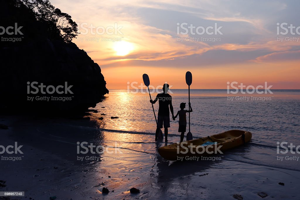 Man and daughter kayaking on the beach. stock photo