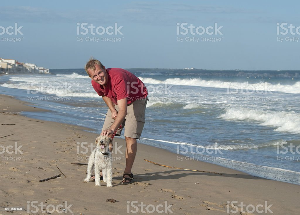 Man and dog enjoy late afternoon walk on beach royalty-free stock photo