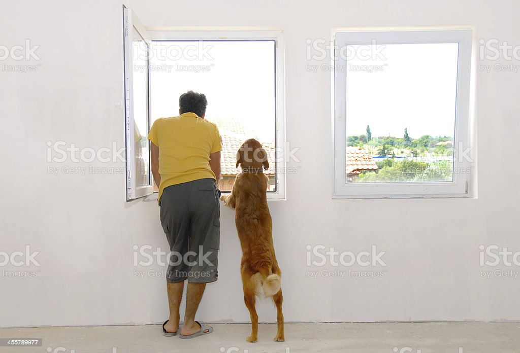 Man and dog looking through window stock photo